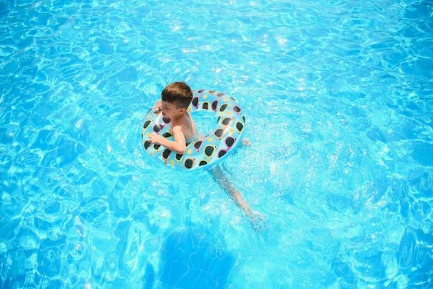 Letnie wakacje dla dzieci. dziecko pływa w basenie. dzieci bawią się w aquaparku.