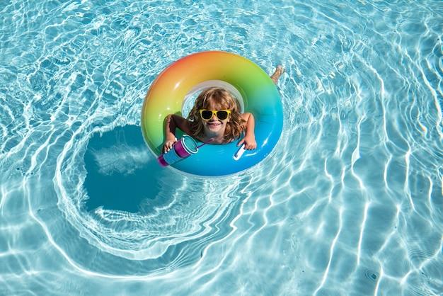 Letnie wakacje dla dzieci letni weekend chłopiec w basenie dzieciak w aquaparku zabawny chłopiec na dmuchanym...