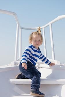 Letnie wakacje dzieciństwo szczęście szczęśliwy mały chłopiec na jachcie wycieczka łodzią przez morze lub ocean zabawny dzieciak