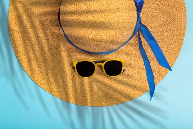 Letnie wakacje i koncepcja słońca. czapka damska z okularami przeciwsłonecznymi i cieniem gałęzi tropikalnego drzewa na czystym niebieskim tle. relaks, wakacje, pomysł na plażę. zdjęcie wysokiej jakości