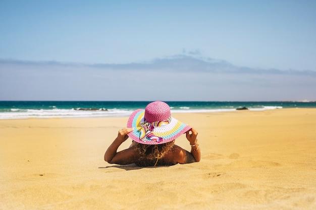 Letnie wakacje i ludzie odpoczywają w koncepcji plaży z kobietą oglądaną z tyłu opalają się na piasku z morzem i błękitnym niebem w scenie