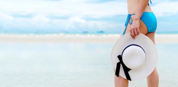 Letnie wakacje kobieta na plaży. wesoła kobieta nosi bikini i trzyma słomkowe kapelusze