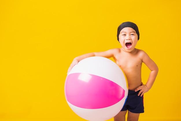 Letnie wakacje koncepcja portret szczęśliwy słodkie małe dziecko chłopiec uśmiechający się w stroju kąpielowym trzymać piłkę plażową