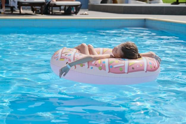 Letnie wakacje, mała dziewczynka spoczywa na pierścieniu w odkrytym basenie, hotel uzdrowiskowy