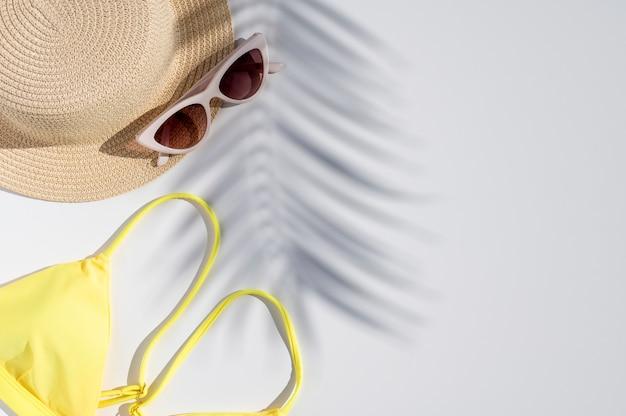 Letnie wakacje minimalne płaskie. modna palma pozostawia cienie na słomkowym kapeluszu, okularach przeciwsłonecznych i bikini z wolnym miejscem na tekst. szablon projektu. makieta widoku z góry