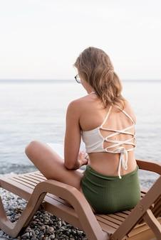 Letnie wakacje na plaży. piękna młoda kobieta w kostiumie kąpielowym siedząca na leżaku, czytająca książkę i relaksująca, niebieska godzina