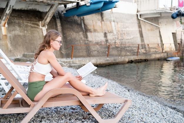 Letnie wakacje na plaży. piękna młoda kobieta w kostiumie kąpielowym, siedząca na leżaku, czytająca książkę i relaksująca