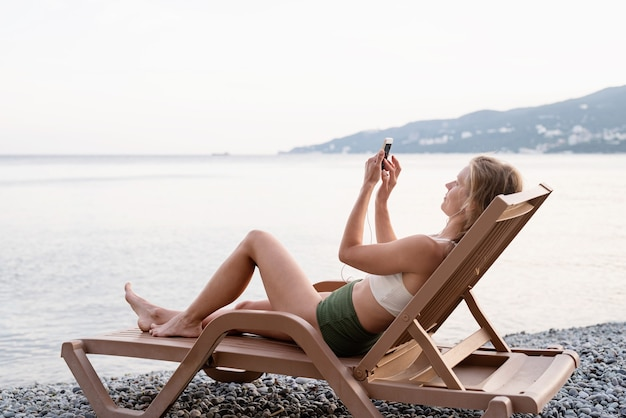 Letnie wakacje na plaży. piękna młoda kobieta w stroju kąpielowym leżąca na leżaku słuchająca muzyki za pomocą urządzenia mobilnego, niebieska godzina