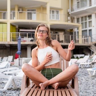 Letnie wakacje na plaży. piękna młoda kobieta w stroju kąpielowym siedząca na leżaku, słuchająca muzyki za pomocą urządzenia mobilnego i tańcząca, niebieska godzina