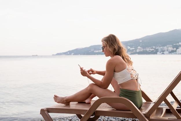 Letnie wakacje na plaży. piękna młoda kobieta w stroju kąpielowym siedząca na leżaku słuchająca muzyki za pomocą urządzenia mobilnego, niebieska godzina