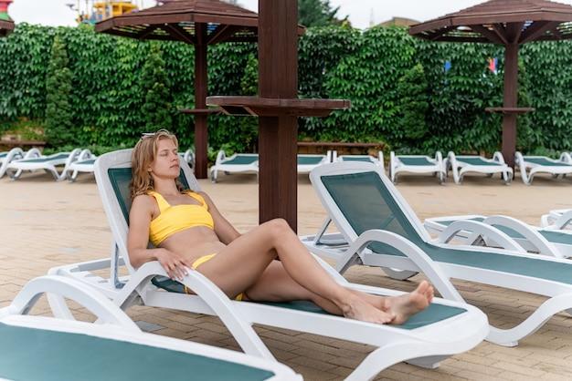 Letnie wakacje na plaży. piękna młoda kobieta w żółtym stroju kąpielowym leżąca na leżaku przy basenie