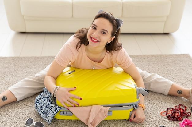 Letnie wakacje, podróż i koncepcja podróżnika. młoda piękna kobieta zbiera walizkę latem