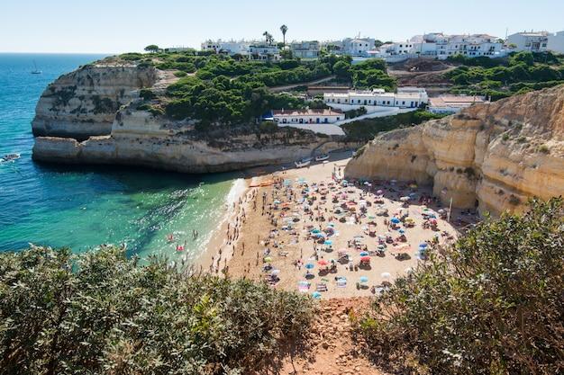 Letnie wakacje w portugalii. tłum kąpiących się na plaży benagil w algarve