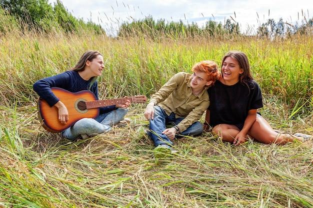 Letnie wakacje wakacje muzyka koncepcja szczęśliwych ludzi. grupa trzech przyjaciół chłopca i dwie dziewczyny z gitarą śpiewa piosenkę zabawy razem na świeżym powietrzu. piknik z przyjaciółmi na wycieczce na łonie natury.