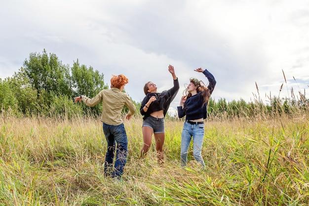 Letnie wakacje wakacje szczęśliwych ludzi koncepcja. grupa trzech przyjaciół chłopca i dwie dziewczyny tańczą i bawią się razem na świeżym powietrzu. piknik z przyjaciółmi na wycieczce na łonie natury.