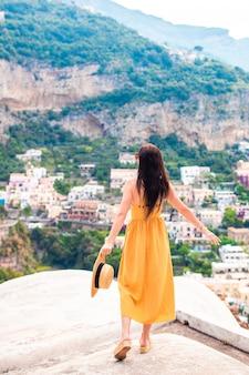 Letnie wakacje we włoszech. młoda kobieta w positano wiosce na tle, amalfi wybrzeże, włochy