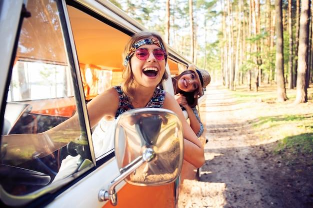 Letnie wakacje, wycieczka samochodowa, wakacje, podróże i koncepcja ludzi - przyjaciele hipster na wycieczkę w letni dzień