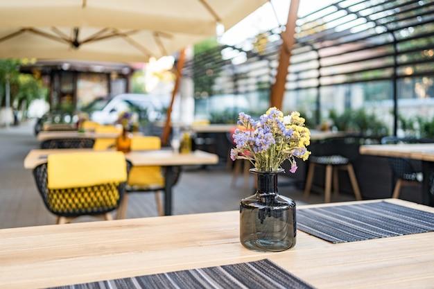 Letnie wnętrze kawiarni ulicznej na ulicy, ozdobione ozdobnymi drzewami i parasolami