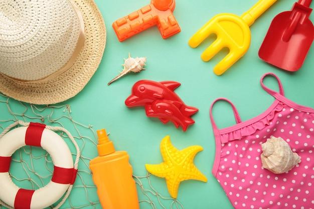 Letnie zabawki plażowe z akcesoriami na miętowym tle. widok z góry