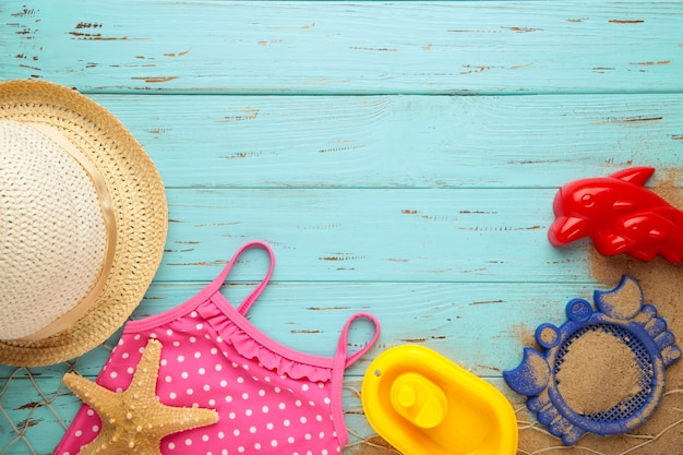 Letnie zabawki plażowe z akcesoriami na niebieskim tle drewnianych z miejsca kopiowania. ramka letnia