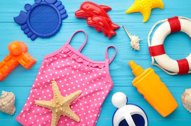 Letnie zabawki plażowe z akcesoriami na niebieskim tle. widok z góry