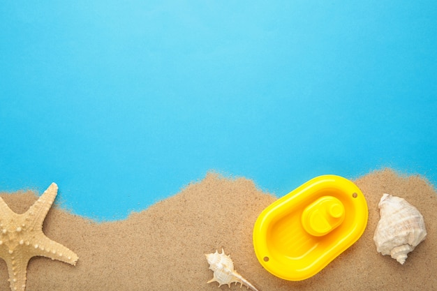 Letnie zabawki plażowe z akcesoriami na niebieskim tle z miejsca na kopię. ramka letnia