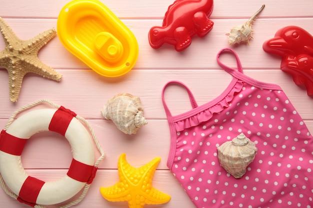 Letnie zabawki plażowe z akcesoriami na różowym tle. widok z góry