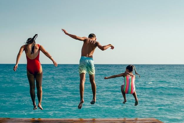Letnie zabawy dzieci skaczące do wody patrzą od tyłu