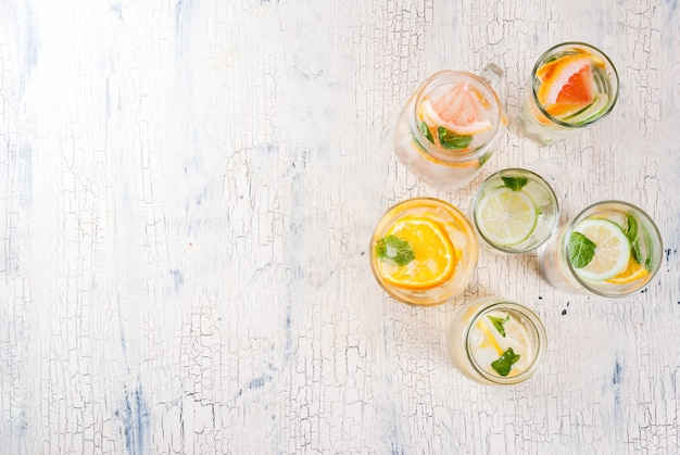 Letnie zdrowe koktajle, zestaw różnych wód cytrusowych, lemoniady lub mojito, z limonkowo-cytrynowym grejpfrutem, dietetyczne napoje detoksykacyjne, w różnych szklankach jasnego tła