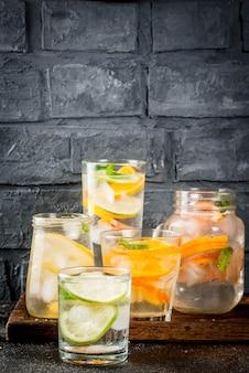 Letnie zdrowe koktajle, zestaw różnych wód cytrusowych, lemoniady lub mojito, z limonkowo-cytrynowym grejpfrutem, dietetyczne napoje detoksykacyjne, w różnych szklankach