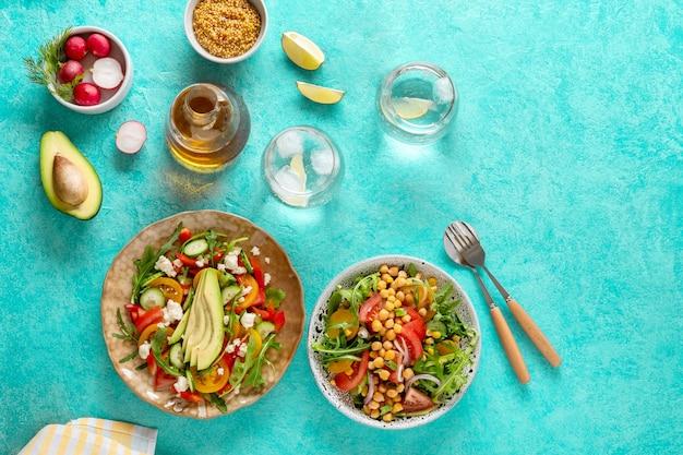 Letnie zdrowe sałatki warzywne z awokado, ogórkiem, rzodkiewką, papryką i pomidorem. letnia zdrowa sałatka jarzynowa. zdrowa żywność.widok z góry.