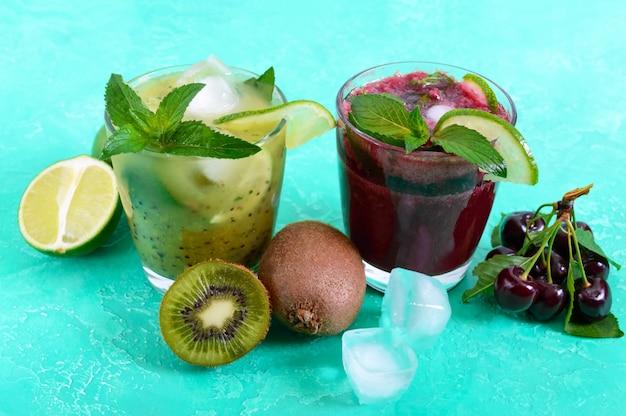 Letnie zimne napoje ze świeżymi owocami, jagodami i miętą. koktajle wiśniowe, koktajl kiwi w szklankach.