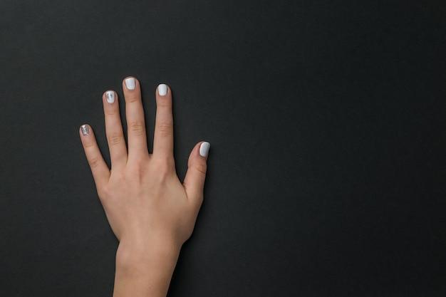 Lewa ręka dziewczyny z lekkim manicure na czarno. dbaj o dłonie.
