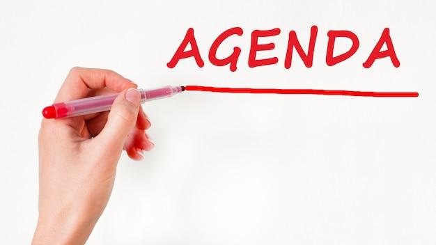 Lewa ręka, pisanie agendy napis z czerwonym znacznikiem koloru, koncepcja, obraz pień