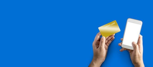 Lewa ręka trzyma złotą kartę kredytową, prawa ręka trzyma biały telefon komórkowy, izolowany na niebieskim tle i ścieżkę przycinającą.