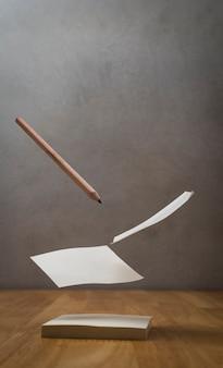 Lewitacja obrazek notepaper i ołówek na drewnianym stole