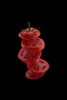 Lewitacja świeżego pokrojonego pomidora. latające plastry pomidora na białym tle