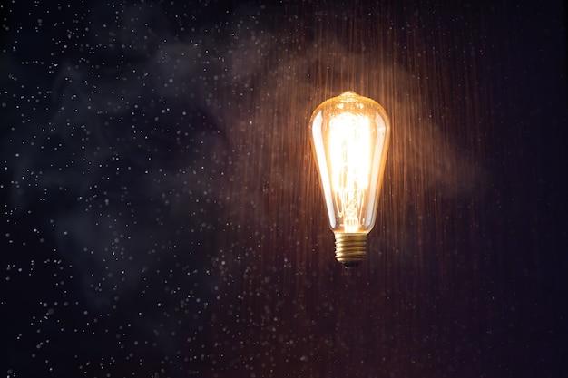Lewitująca żarówka świeci bez przewodów. na tle efekt deszczu i dymu