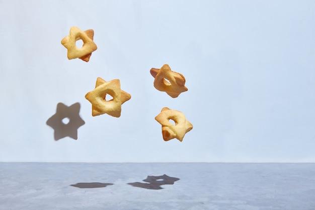 Lewitujące ciasteczka w kształcie sześciokątnej żydowskiej gwiazdy dawida. heksagram. skopiuj miejsce