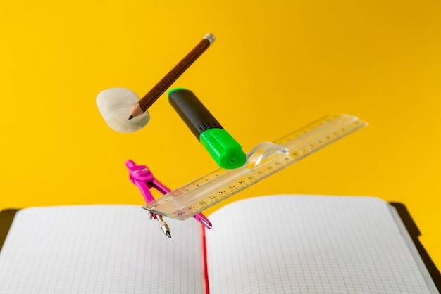 Lewitujące przybory szkolne do matematyki na żółtym tle. edukacja i kreatywność