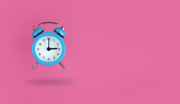 Lewitujący niebieski budzik na różowym tle z miejsca na kopię.