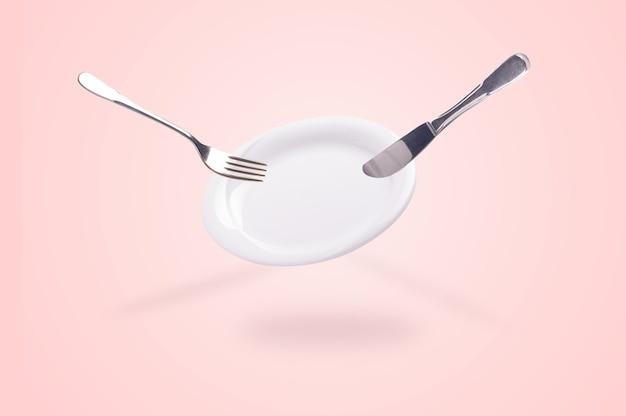 Lewitujący pusty talerz z nożem i widelcem na różowym tle, czysta koncepcja naczyń kuchennych