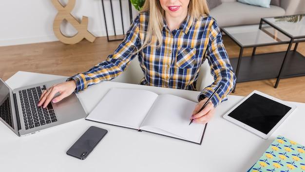Leworęczna kobieta pisze w notesie w miejscu pracy z laptopem