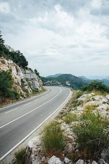 Lewy zakręt górskiej autostrady z błękitnym niebem i morzem