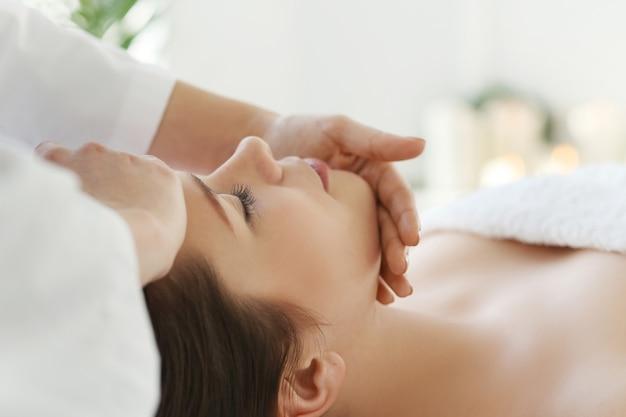 Leżąca kobieta otrzymująca masaż. terapia czaszkowo-krzyżowa