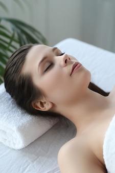 Leżąca kobieta przygotowana do zabiegu kosmetycznego