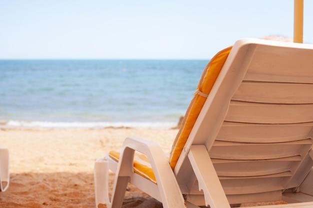 Leżak do odpoczynku. błękitne morze i piasek. słoneczna upalna pogoda. spokojny i cichy