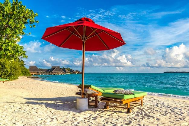 Leżak i parasol na tropikalnej plaży na malediwach