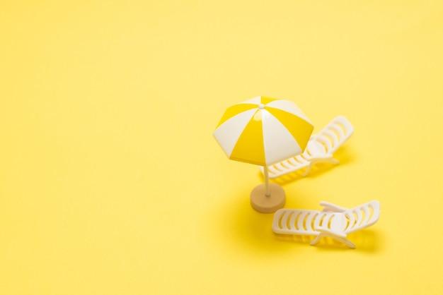 Leżak i żółty parasol na żółtym tle.