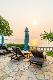 Leżak lub łóżko basenowe z parasolem wokół basenu z widokiem na zachód słońca i morze